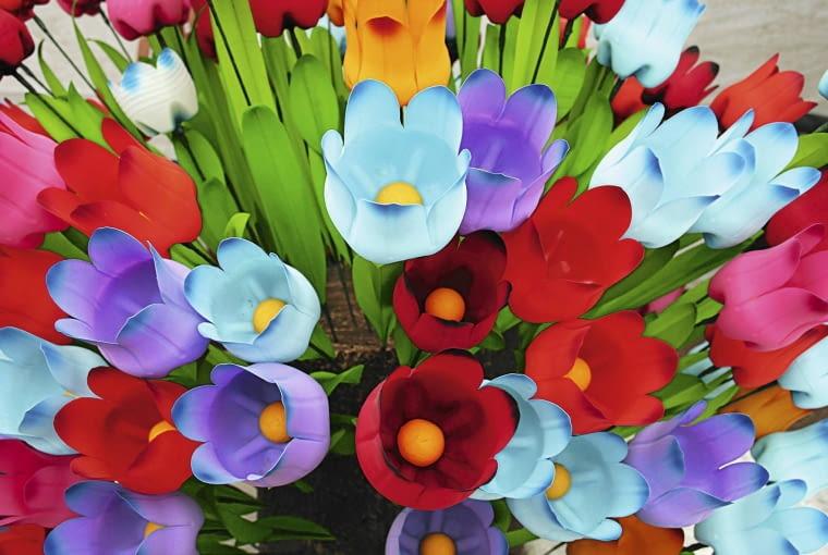 TULIPANY NA LATA ODCIĘTE DENKA KOLOROWYCH BUTELEK mogą rozkwitnąć niczym kwiaty. Wcześniej wycinamy ich brzegi na kształt płatków, przedziurawiamy środki i nawlekamy na drut, na który nabijamy np. żółte kapsle. Kwiaty można też pomalować.