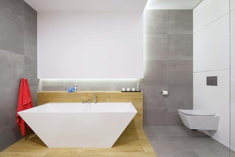Urodę i oryginalną formę eleganckiej wanny podkreślono sposobem wykończenia wnętrza. Przypominające drewno płytki podłogowe wraz z 'tektonicznym', opadającym na ścianę sufitem tworzą piękną oprawę dla tego designerskiego łazienkowego urządzenia