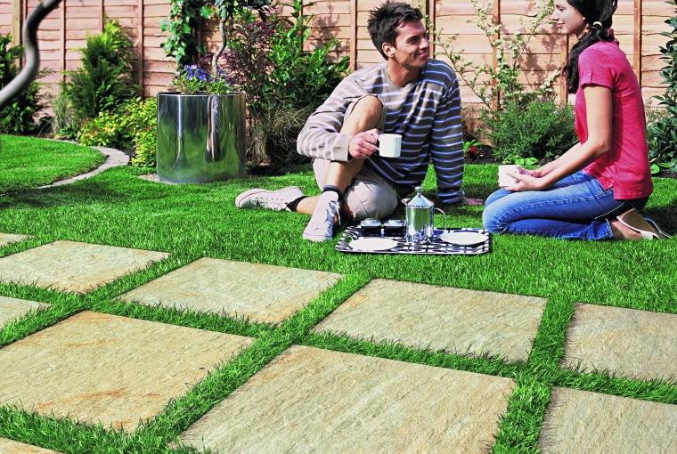 Ekologiczna posadzka z betonowych płyt. Odstępy pomiędzy nimi wypełniono ziemią i obsiano trawą.