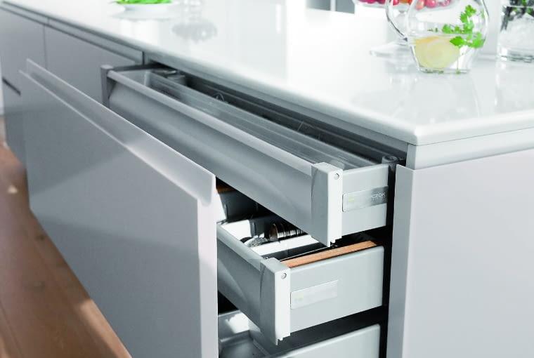 ZAMIAST SZAFEK zaprojektowano wwyspie praktyczne ipojemne szuflady systemowe. Otwierają się lekko iłatwo; wewnątrz mają specjalne wkłady, które ułatwiają przechowywanie sztućców, talerzy, garnków itp.