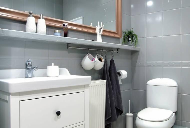 PO ZMIANIE. Duże lustro, oświetlone dwoma kinkietami, zapewnia pani domu dobre warunki do dbania o urodę. Na relingu pod półką można wieszać ręczniki oraz pojemniki z kosmetykami. OLYMPUS DIGITAL CAMERA