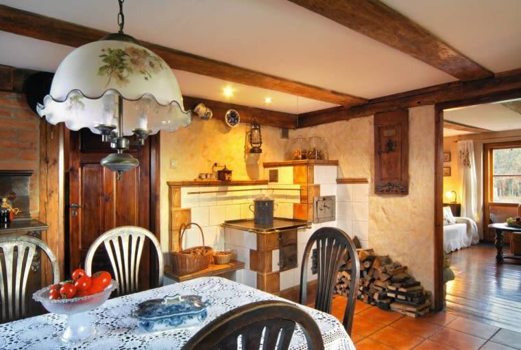 DOM. Piec kaflowy, choć wygląda nabardzo stary, został zbudowany współcześnie. Właściciele używają go na co dzień, bo doskonale dogrzewa wnętrza, mogą też upiec w nim chleb. Drewniana ozdoba na ścianie obok tofragment starych drzwi. Piękny koronkowy obrus i firanki pasują jakulał do kuchennej aranżacji.