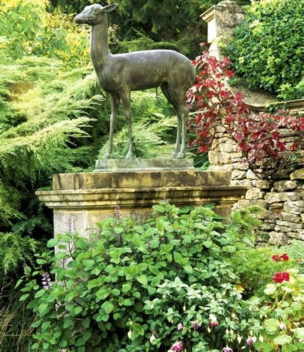 Bronze deer, one of a pair of copies of those from the villa of the Papyril in Pompeii, beside steps ascending the gardens terraces - Iford Manor, Bradford-on-Avon, Wiltshire