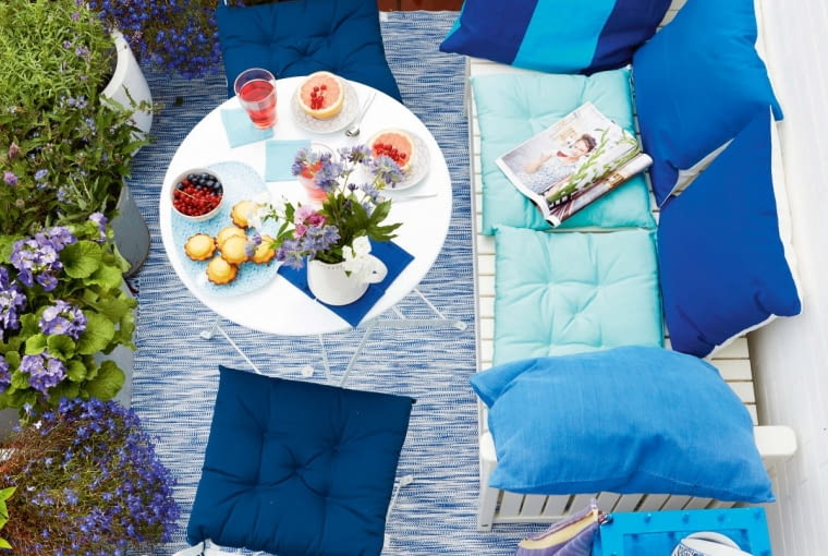 jA summery balcony seen from above with a laid table and aqua coloured cushions on white, outdoor furniture