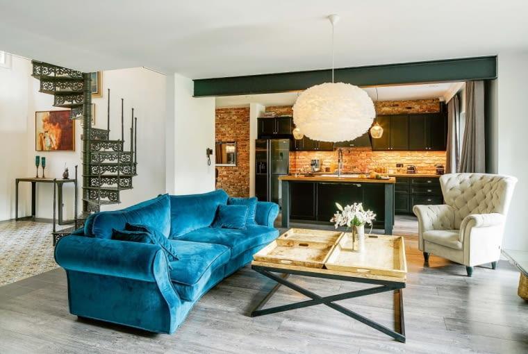Obok foteli, sof i puf uwagę zwraca ława na sprzęt grający oraz stolik kawowy - przykład inwencji właścicieli. Salon otwiera się na kuchnię, stanowiącą zaproszenie do nieco innego świata