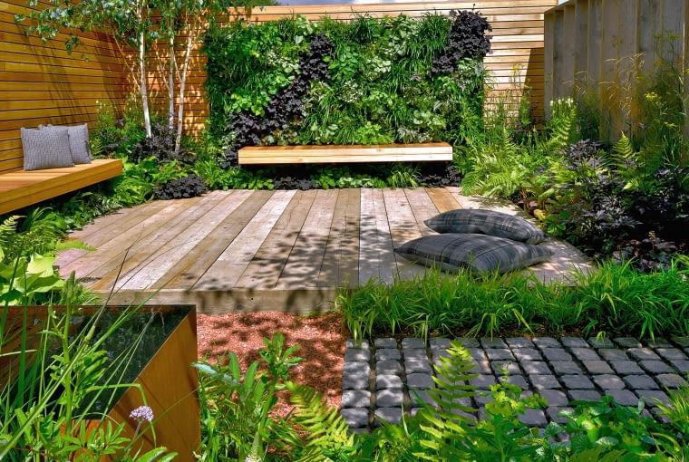 Nowoczesny ogród może być przytulny, wystarczy zastosować w nim drewno, a na ścianie powiesić 'obraz' z żywych roślin.