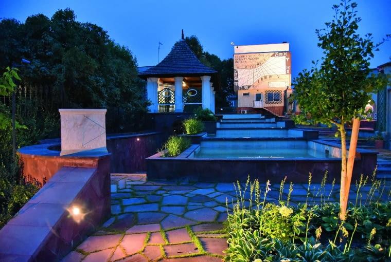 Po zmierzchu ogród nabiera tajemnego uroku, rozjaśniony światłem dyskretnie rozmieszczonych lamp.