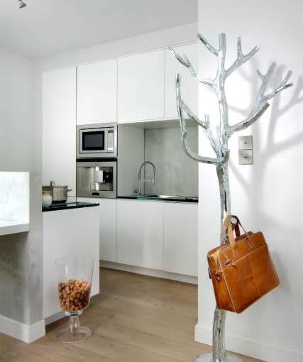 KUCHNIA: Cała w bieli. Murek oraz ścianę nad zlewem pokrywa tynk strukturalny imitujący beton. Zabezpieczono go lakierem i gdzieniegdzie ozdobiono mieniącymi się plamkami srebrnej farby.