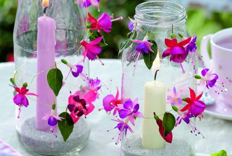 """Efektowna """"pochodnia"""" z butelki ozdobiona kwiatkami fuksji to jasny punkt programu wieczornego przyjęcia."""