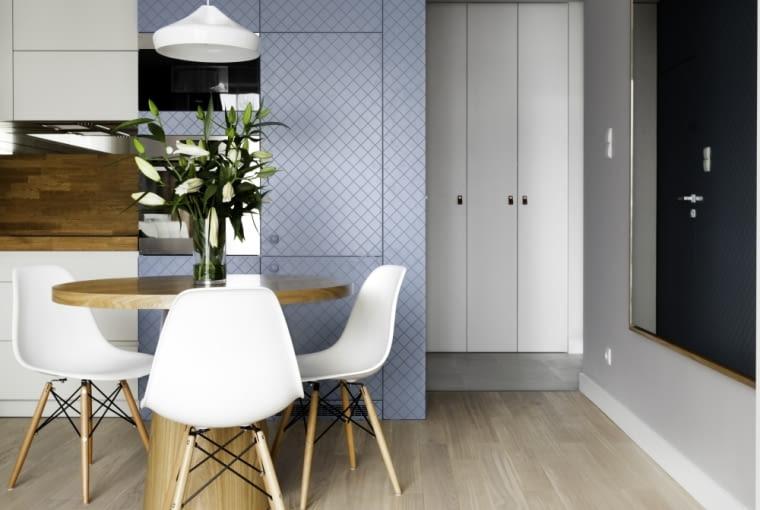Ozdobą kuchni są designerskie, białe krzesła na drewnianych nogach.