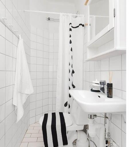 Czerń i biel to duet zawsze modny! W ten niewielkiej łazience rzuca się w oczy zabawna załona prysznicowa :)