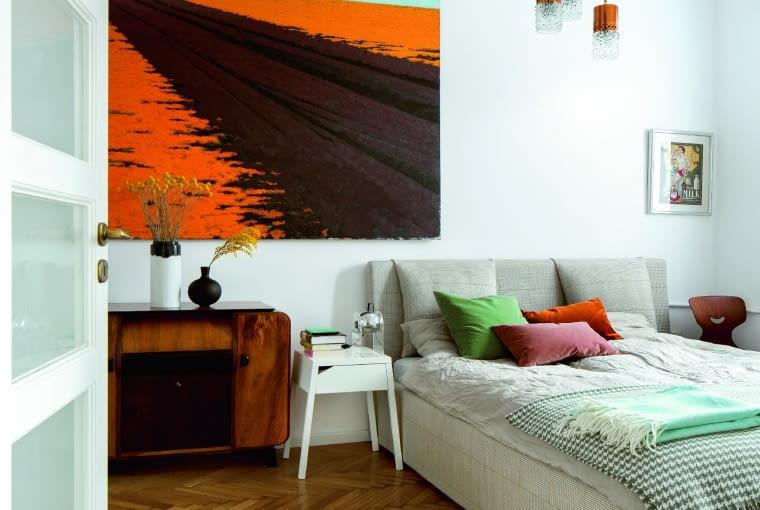 Na podłodze w sypialni (a także w salonie) oryginalny parkiet z lat 50. Łóżko wykonane na zamówienie. Czeska komoda art déco, nad nią obraz Antoniego Starowieyskiego, żyrandol z lat 70.