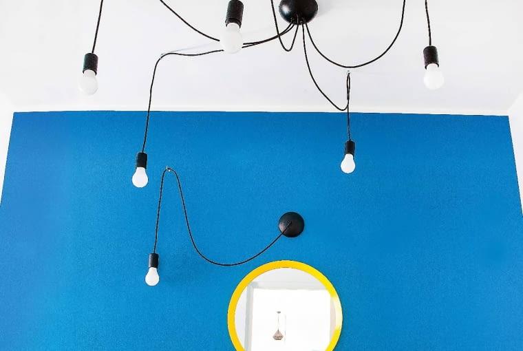 Lampa-pająk (jasnociemno.pl) pozwala Bartoszowi ustawić światło tak, jak chce. Do kompletu projektantka dokupiła kinkiet z tej samej kolekcji. Lustro w żółtej ramie (IKEA) ładnie prezentuje się na tle niebieskiej ściany - wygląda jak słońce na bezchmurnym kobaltowym niebie.