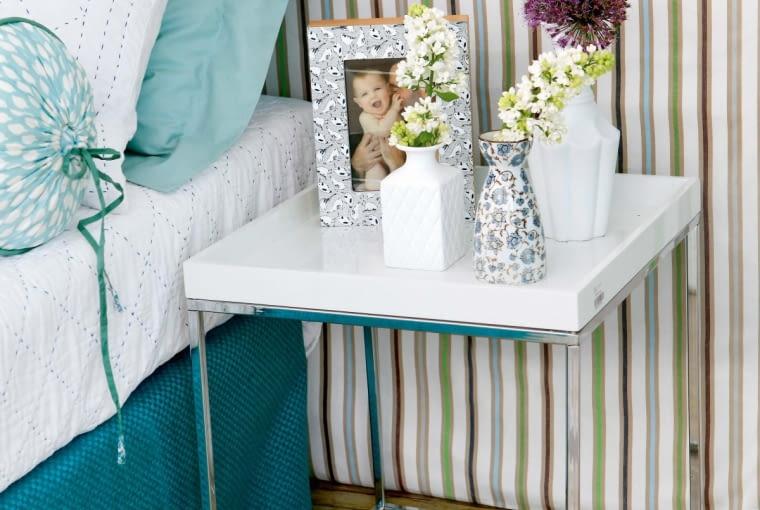 Kiedy regaliki, pełniące przedtem funkcję stolików nocnych, zostały wbudowane wzagłówek, trzeba było je zastąpić innymi mebelkami. Zjednej strony łóżka stanął prosty stolik zbiałym blatem na metalowej podstawie.
