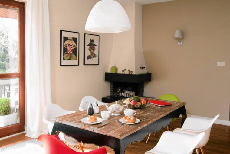 adalnię urządzono w drugiej części salonu, w pobliżu kominka obudowanego klinkierem i granitem. Posiłki rodzina jada przy oryginalnym stole z przecieranym blatem i wygiętymi nogami, do którego gospodarze dobrali lekkie krzesła Eiffel Wood Arm (inspirowane projektem Eamesów).