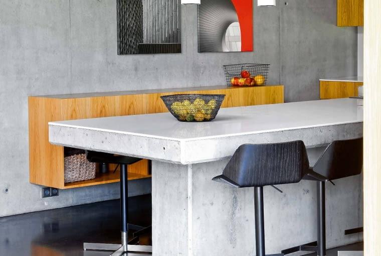Wyspa kuchenna - zakotwiony w posadzce betonowy odlew nakryty płytą białego corianu. Na ścianie fotografie - detale architektury - autorstwa Macieja Siczka.