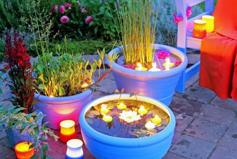 """Gdy miejsca jest mało, wystarczy pojemnik z wodą, pływające świeczki i główki kwiatów. W donicy (z warstwą podłoża na dnie) można też posadzić rośliny wodne - taki """"żywy"""" lampion będzie z pewnością bardziej efektowny od zwykłego świecznika."""