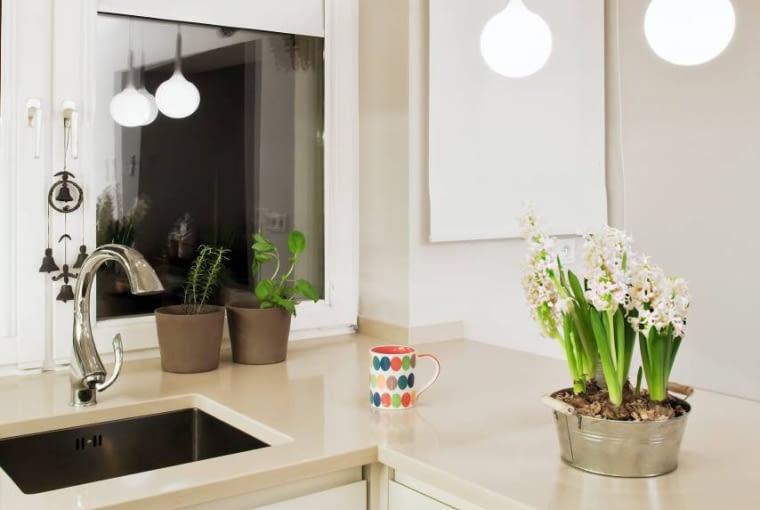 Kuchnie. Blat barku usytuowanego w sąsiedztwie okna, służący też jako dodatkowe miejsce do pracy, po zmroku oświetlają lampy wiszące z oryginalnymi kloszami w kształcie dużych kropli. W dzień przez dwa okna wpada do wnętrza dużo naturalnego światła. Pod jednym z okien jest zlewozmywak z wyjmowaną baterią, umożliwiającą otwieranie skrzydła.