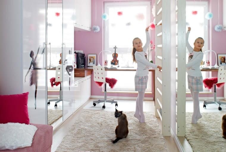 W biało-różowym pokoju 9-letniej Oliwki zamontowano drabinkę i duże lustra, tak by początkująca baletnica i gimnastyczka artystyczna miała odpowiednie warunki do ćwiczeń. Na zdjęciu Oliwce towarzyszy kot Marcel. Front szafy zdobi nadrukowana primabalerina.