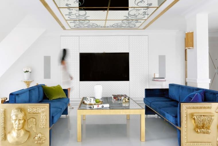 Lustro sufitu pomnaża itak dużą przestrzeń salonu. Sofy, zainspirowane modelem Versailles, portugalski producent Boca do Lobo wykonał na zamówienie za pośrednictwem firmy Heban. Drewniane reliefowane elementy boczne zostały na prośbę klienta pokryte płatkami 24-karatowego złota.