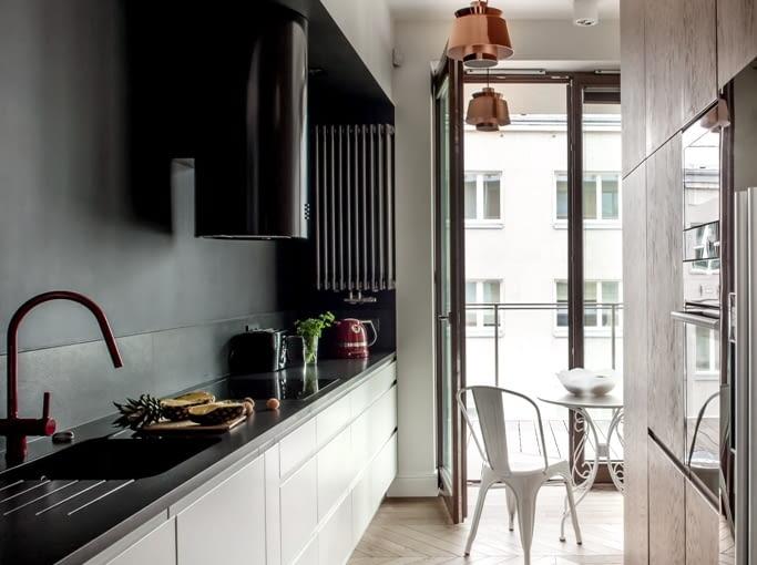 Kuchnię od strefy dziennej oddziela ścianka z wysoką zabudową. Kuchenny krajobraz dekorują lampki Utzon Cooper J?rna Utzona (& Tradition) oraz białe metalowe krzesła Tolix Xaviera Paucharda.