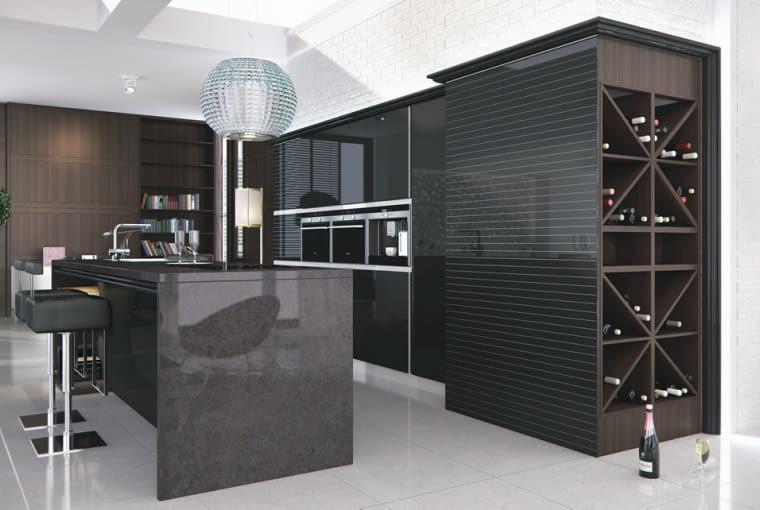 Styl: jak w nowoczesnym salonie <BR > Współczesna kuchnia otwiera się na pokój dzienny i tworzy z nim spójną całość - stąd pojawiające się na zabudowie rozmaite zdobienia, jakich nie powstydziłyby się meble w salonie. Zabudowa często sięga do sufitu, kryje w sobie nie tylko szafki, ale również urządzenia AGD. We wnętrzu oprócz oświetlenia czysto funkcjonalnego instaluje się dekoracyjne żyrandole. Front wysokiej zabudowy wykończono lakierowanym czarnym szkłem w cienkie paski. Wyspa jest zrobiona z polerowanego granitu. Dla urozmaicenia i kontrastu - kryształowy żyrandol. Zdjęcie: Mebel Rust