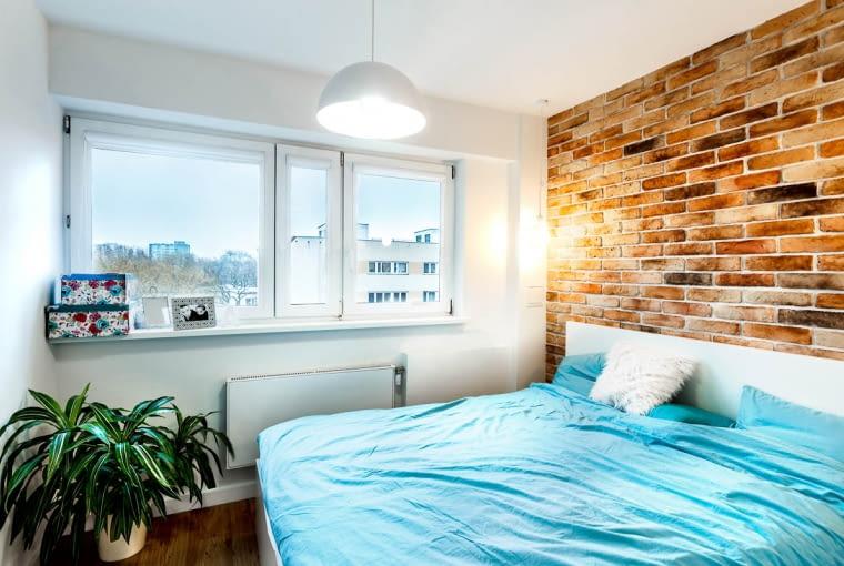 W sypialni jedną ścianę pokrywają czerwone cegły. Powodują one, że w pokoju jest bardzo przytulnie. Dodatkowo czerwień cegieł dobrze się komponuje z błękitem narzuty.