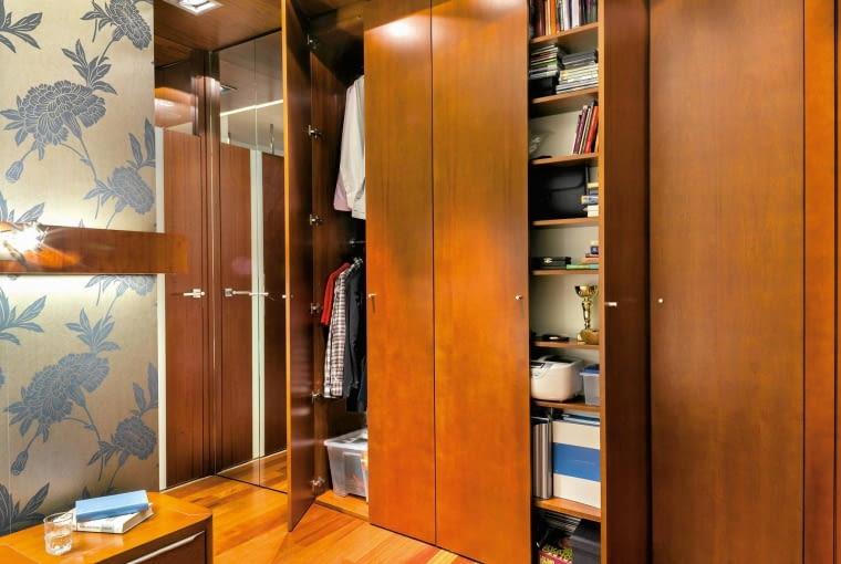 W zabudowie znajdują się wszystkie niezbędne akcesoria: drążki z wieszakami na bluzki i koszule, kosze na bieliznę oraz półki ? zarówno na ubrania, jak i na książki, dokumenty, a nawet sprzęt biurowy. Półki są rozmieszczone na różnej wysokości, aby maksymalnie wykorzystać przestrzeń. Szafa ma także różną głębokość; w głębszej części są drążki z wieszakami, w płytszej półki ? dzięki temu wygodniej się z nich korzysta.