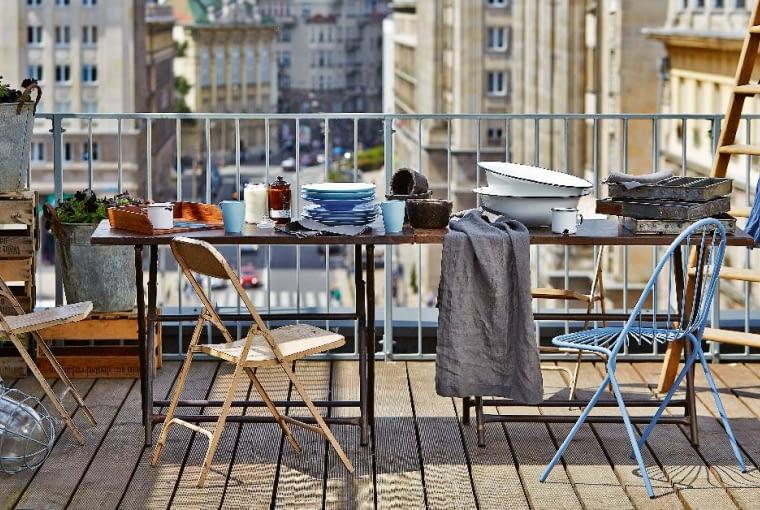 Widok na miasto. Na miejski taras lub balkon salony zwyposażeniem wnętrz Nap polecają składane krzesła One World zkolekcji Nap Concept. Są one ręcznie wykonane zprzetworzonego metalu imożna je składać. Nam bardzo się też podoba błękitne krzesło Drapée francuskiej marki Petite Friture. nap.com.pl