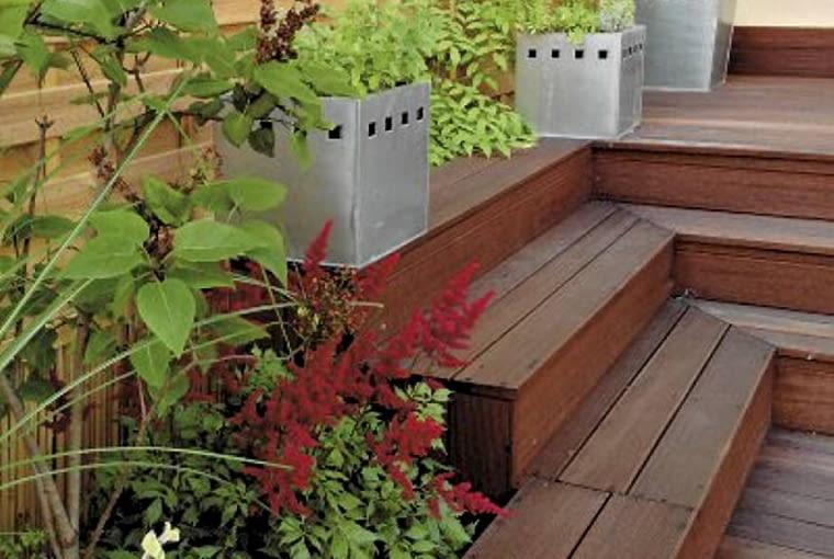 Aranżacje ogrodów. Mały ogród w stylu orientalnym. Taras zbudowano w formie wgłębnika. Dzięki temu jest tu zacisznie, a na drewnianych stopniach można ustawiać donice z roślinami