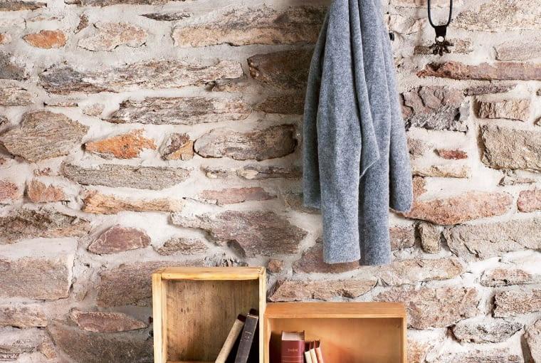 Nieregularne płytki zostały oddzielone od siebie grubą fugą, dzięki czemu ściana przypomina kamienny mur, jakby przeniesiony z francuskiego ogrodu.