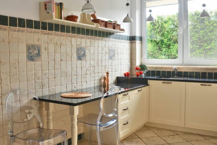 DOM. Wszystkie blaty w kuchni są zrobione z czarnego granitu Galaxy, który połyskuje drobinkami kwarcu. Jako kącik śniadaniowy służy przedłużony blat jednej z szafek (niższej od pozostałych).