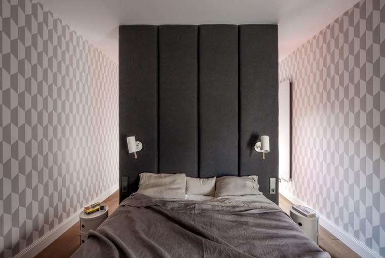 Sypialnia ma oryginalny design. Anna Koszela podzieliła wnętrze na część dzienną i nocną za pomocą wełnianej ściany. Dzięki temu rozwiązaniu nie było potrzeby instalacji drzwi, a część nocna mimo braku okna jest dobrze doświetlona. Efekt głębi uzyskano przy użyciu trójwymiarowej tapety Cole&Son, pokrywającej ściany sypialni.