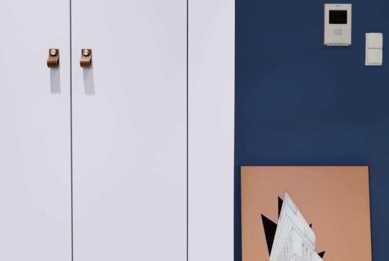 Biała szafa świetnie prezentuje się na tle ciemnoniebieskiej ściany.