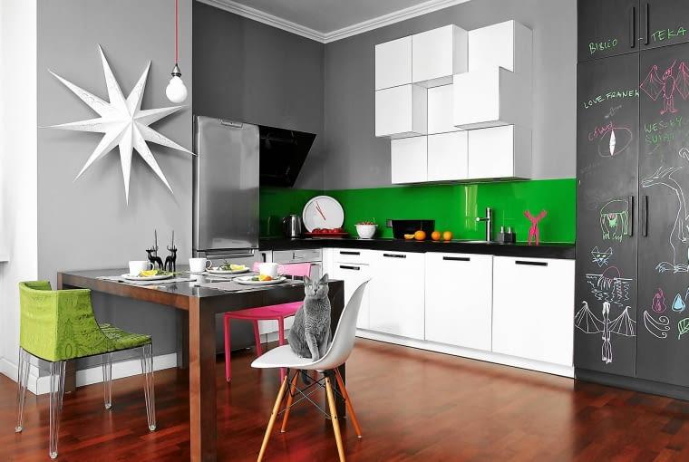 Białe meble kuchenne i szara ściana z akcentem zieleni.