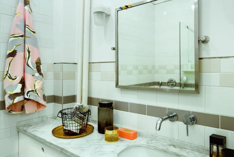 """W niewielkiej łazience marmurowy blat harmonizuje z klasycznymi płytkami w formie """"cegiełek"""" i kwadratów, geometryczny ornament nawiązuje kolorystyką do lat 50. Kinkiety Zangra (Intterno home). W przedpokoju zabudowę regału uzupełnia zawieszona na ścianie szafka na buty Intterno."""