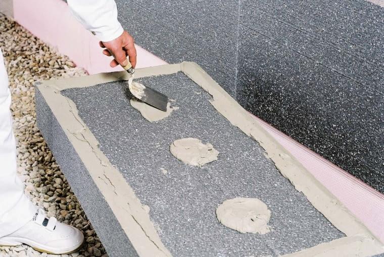 Do przyklejania płyt zaleca się metodę obwodowo-punktową, czyli ramkę na obrzeżu i wewnątrz placki zaprawy, z pokryciem minimum 40% powierzchni płyty