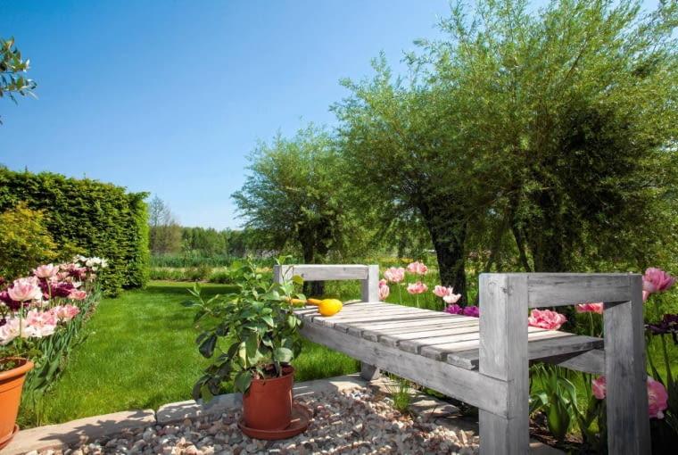 BLISKO DOMU JEST MIEJSCE na mały design - stoją tu ciekawe meble ogrodowe, w żwirowych nawierzchniach założono ascetyczne kompozycje roślin i posadzono trochę kwiatów.