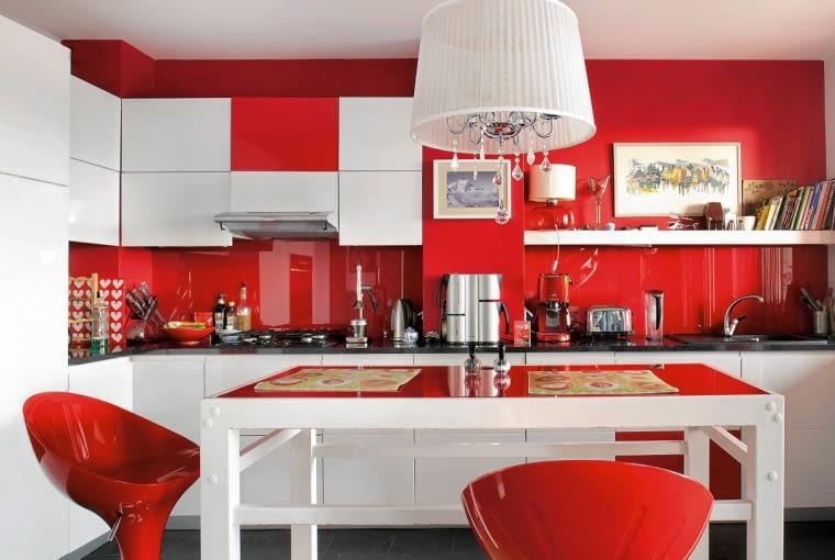 Białe meble kuchenne i czerwone ściany