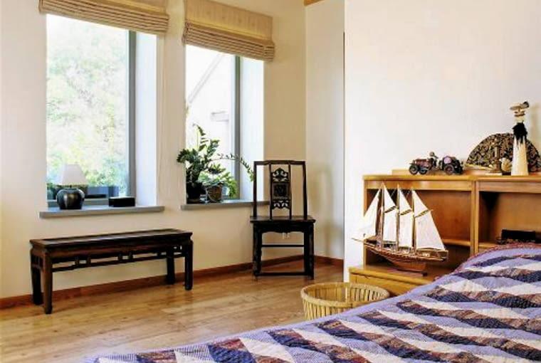 Sypialnia gospodarzy. Ścianka kurtynowa wyznaczająca wezgłowie łóżka kryje sporej wielkości garderobę