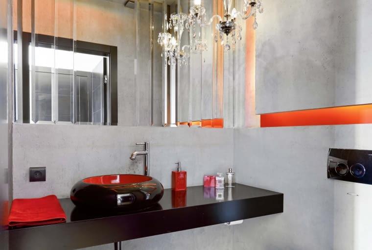 ŚCIANY W TOALECIE wykończono betonem. Jego szarą barwę ożywiają akcenty oranżu i czerwieni - takie kolory mają m.in. podświetlane wnęki i wnętrze umywalki (Artvillano). Kryształowy żyrandol został wyszukany na pchlim targu. Klejone do ściany lustro, podzielone na fazowane pasy pionowe pasy, to projekt gospodyni. Kształty, kształty = oryginalne i przyciągające wzrok. Na przykład umywalka wyglądająca jak misa albo patera.