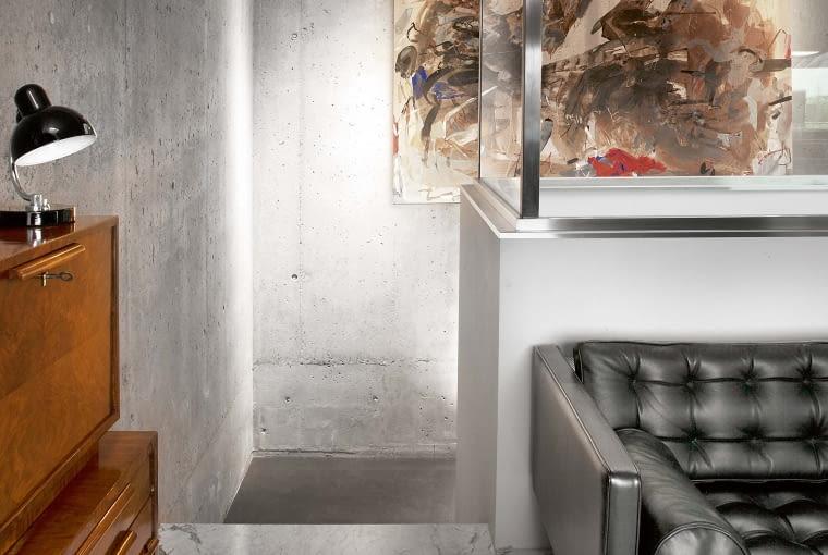 Na sąsiedniej stronie: W korytarzu łączącym oba mieszkania pozostawiono fragment surowej betonowej posadzki, która kontrastuje z gładkością marmuru. W głębi obraz 'Pejzaż' Marzeny Jagiełło.