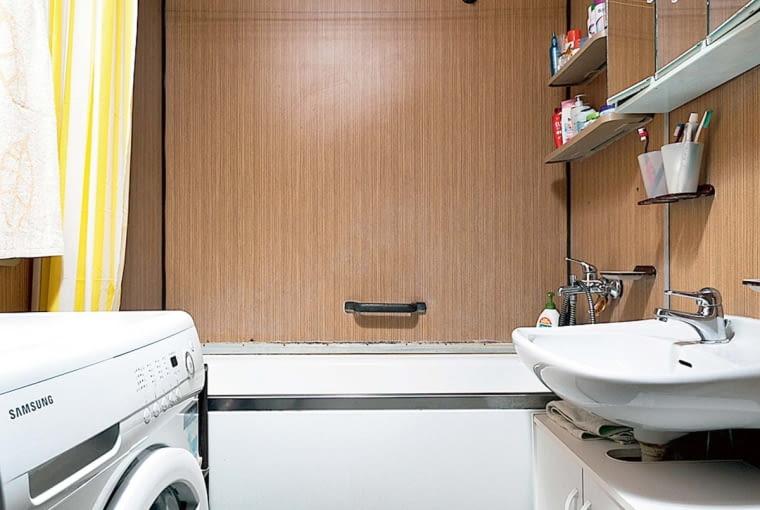 Przed remontem. Rozmieszczenie sprzętów nie było zbyt wygodne. Wchodziło się prosto na umywalkę i pralkę usytuowane naprzeciwko siebie. Ścianę w głębi zajmowała wanna.