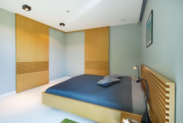 W sypialni właścicieli zamontowano wielkie, przesuwne, drewniane moduły. Jeden zasłania telewizor na ścianie, drugi wejście do garderoby
