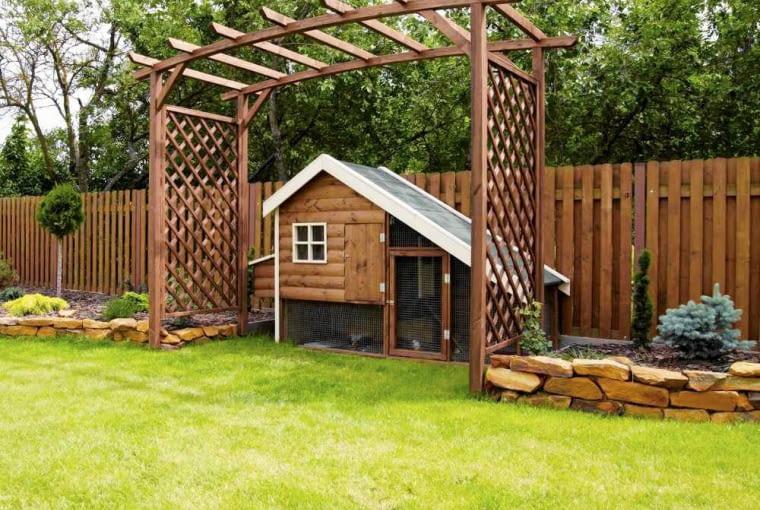 Taka drewniana ażurowa altanka, połąączona z domkiem dla dzieci może stać przy samym ogordzeniu