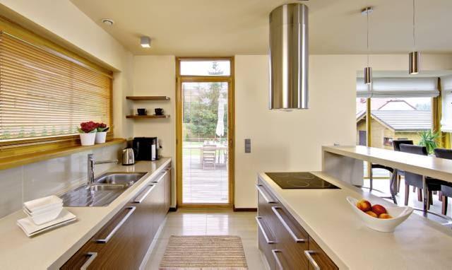 Wysokie drzwi z naświetlem łączące kuchnię z tarasem dodają wnętrzu przestronności. Blaty robocze wykończono nowoczesnym termoformowalnym tworzywem, odpornym na wysoką temperaturę i zaplamienia