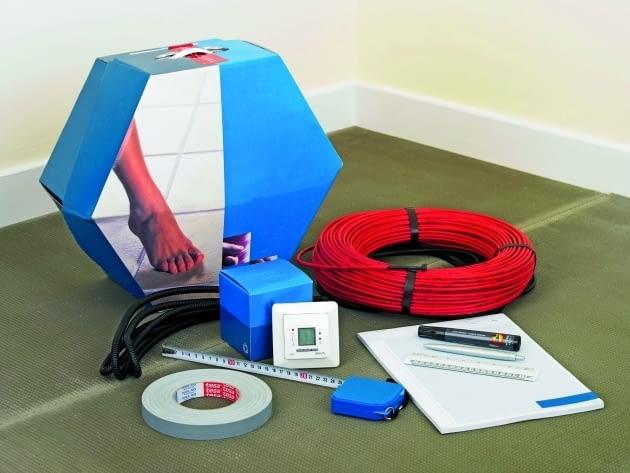 Materiały i przyrządy potrzebne do wykonania ogrzewania podłogowego: przewody grzejne, termostat, peszel do czujnika podłogowego, taśma montażowa, miarka, szkicownik do wykonania projektu rozmieszczenia kabli