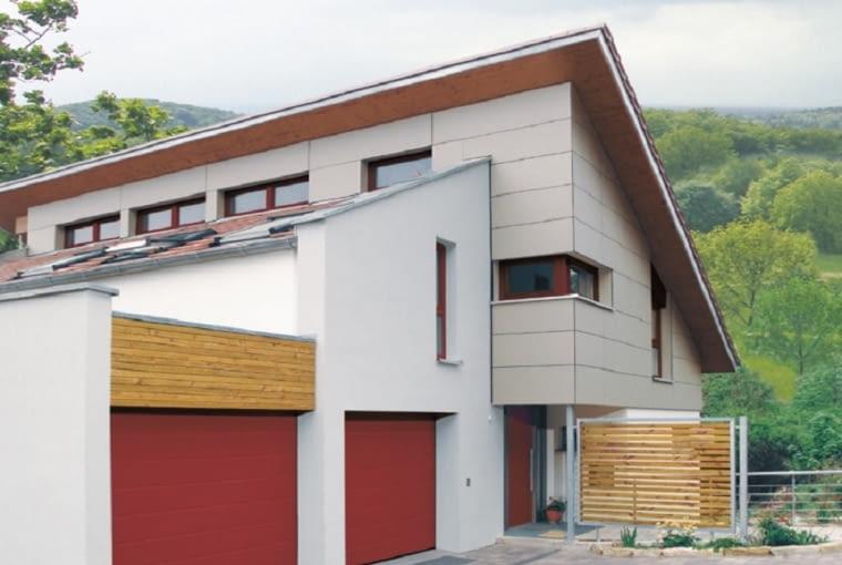 Odważny kolor bram garażowych doskonale komponuje się tu z odcieniem stolarki okiennej i drzwiowej