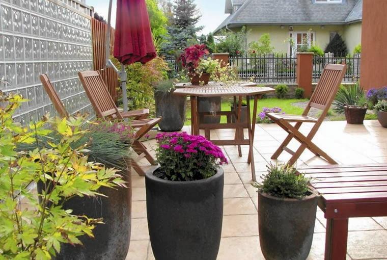 Taras oddzielony został od sąsiadów ścianą z luksferów. W sezonie zdobią go donice pełne kwitnących roślin. Projekt ogrodu