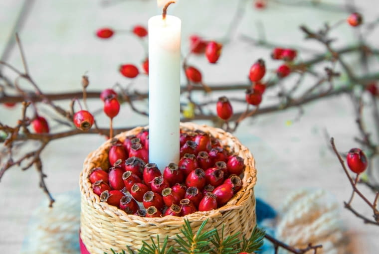 HCandle mounted in a woven basket containing Crataegus - Hawthorn berries